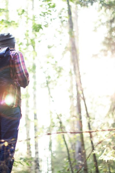 A person standing next to a forest